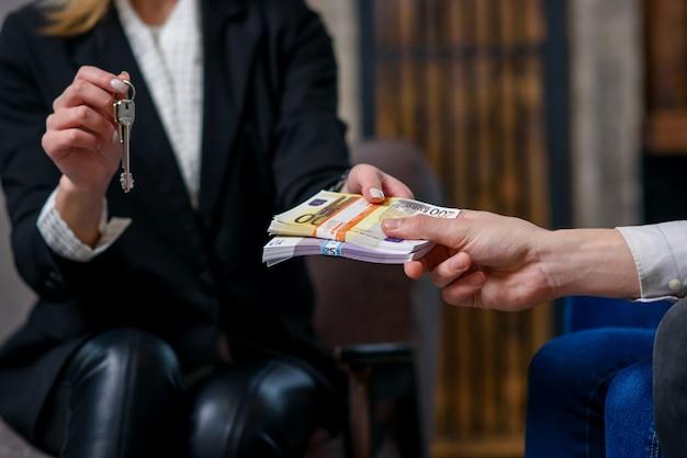 Agente immobiliare femminile che fornisce chiave dall'appartamento, casa mentre clienti maschii che danno soldi.