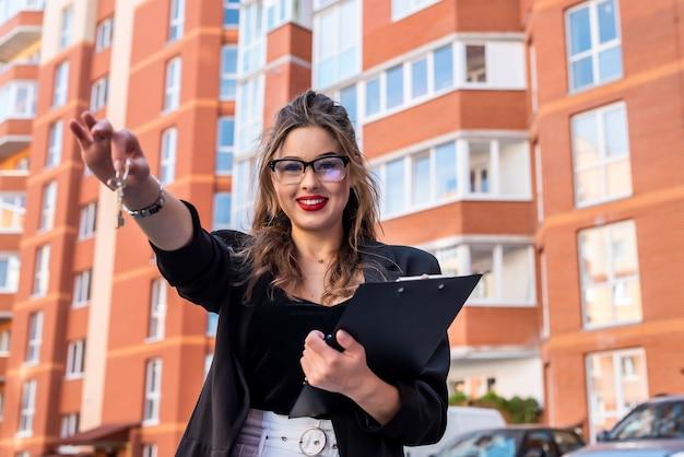 Agente immobiliare femminile che tiene portachiavi a forma di piccola casa e chiavi contro casa come sfondo