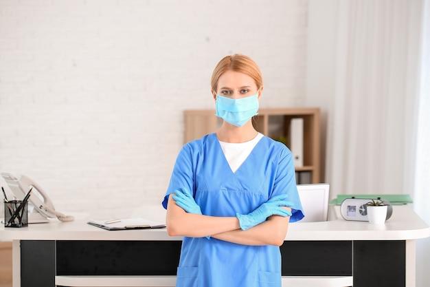 Receptionist femminile vicino alla scrivania in clinica Foto Premium
