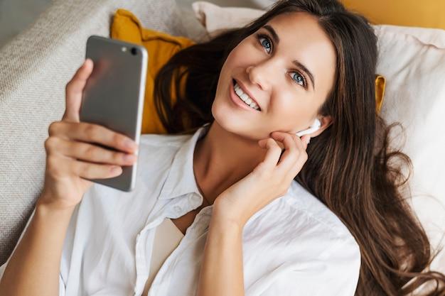 Donna che si rilassa a casa, utilizza lo smartphone per inviare messaggi di testo, condividere foto, comunicare con gli amici, controllare la posta elettronica, guardare video, giocare online. opportunità di intrattenimento su gadget connessi al web.