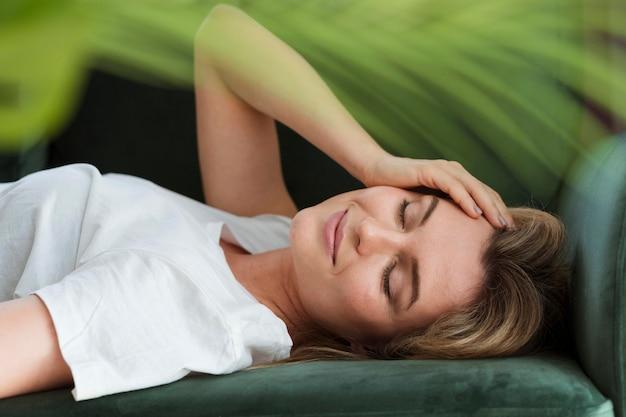 Riposo femminile sul divano e pianta sfocata