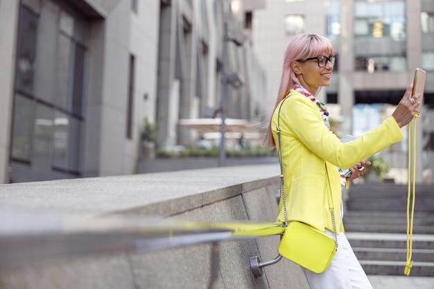 Donna che riposa alla ringhiera delle scale e scatta foto con lo smartphone