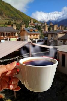 Mano femminile che tiene una tazza di caffè caldo con vapore contro la vista sfocata del paese country