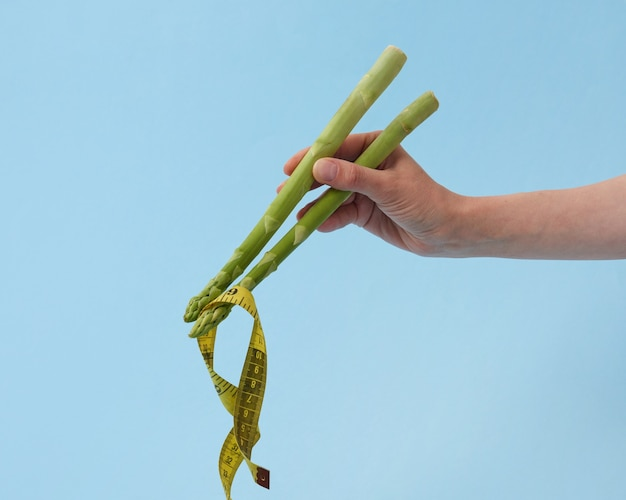 La mano della femmina con i bastoncini degli asparagi sta prendendo il nastro di misura come una tagliatella contro il fondo blu pastello, spazio della copia. nastro di misurazione giallo come cibo giapponese o cinese.
