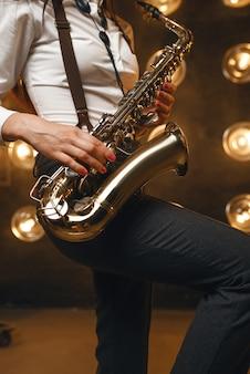Il sassofonista femminile suona il sassofono sul palco con faretti. esecutore jazz che suona sul primo piano della scena