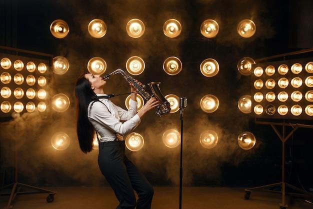 Il sassofonista femminile suona il sassofono sul palco con faretti. artista jazz che suona sulla scena