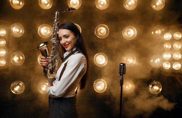 Il sassofonista femminile posa con il sassofono sul palco con faretti. artista jazz che suona sulla scena