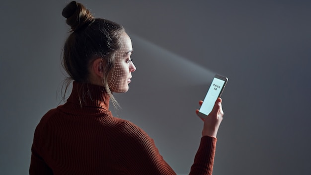 La donna esegue la scansione del viso utilizzando il sistema di riconoscimento facciale sullo smartphone per l'identificazione biometrica. futura tecnologia high-tech e face id
