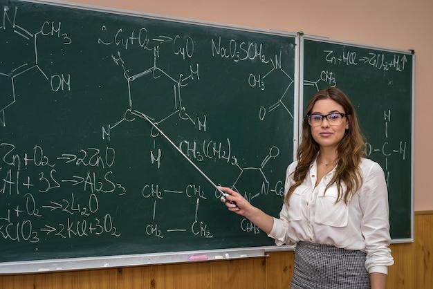 Studentessa di scienze con gli occhiali spiega lezione di chimica a scuola. formazione scolastica