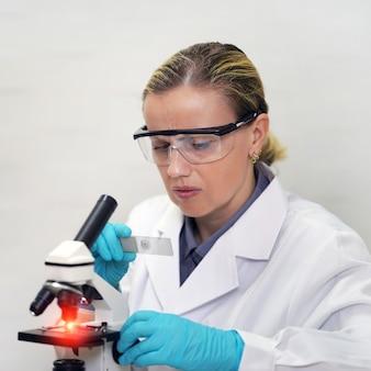 La scienziata è in possesso di un vetrino di prova per un microscopio