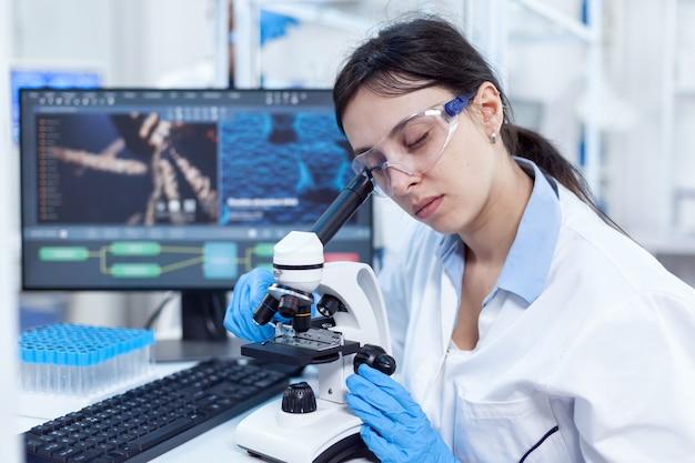 La scienziata nel laboratorio moderno utilizza il microscopio per il vaccino medico. tecnico medico che indossa camice bianco in laboratorio sterile facendo analisi della soluzione.