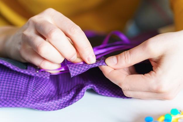 Corsetto di cucito femminile della sarta con l'ago mentre lavora al suo posto di lavoro