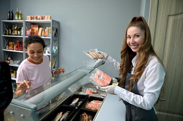 La venditrice nel negozio di pesce tiene tra le mani bistecche di pesce e sorride graziosamente, vendendo i frutti di mare al cliente