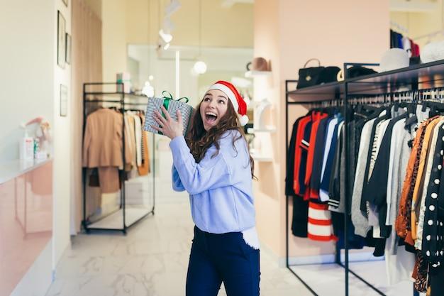 Venditore femminile offre un regalo di natale a un negozio di abbigliamento in abiti natalizi