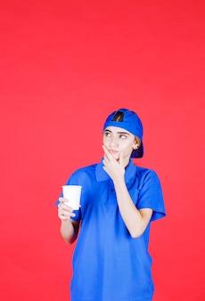 Agente di servizio femminile in uniforme blu che tiene una tazza usa e getta di bevanda e feelin esitazione.