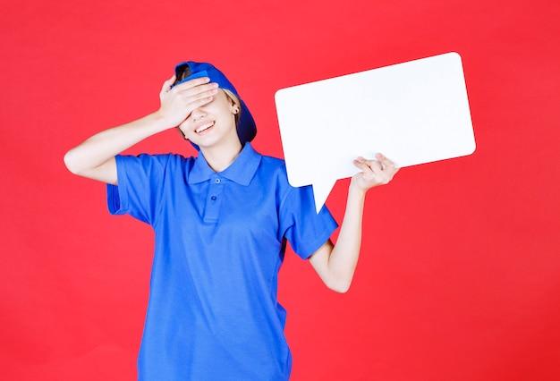 Agente di servizio femminile in uniforme blu che tiene un banco informazioni rettangolo e si copre il viso come stanco.