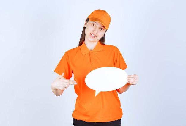 Agente di servizio femminile in dresscode di colore arancione in possesso di un pannello informativo ovale.