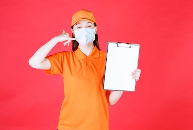 Agente di servizio femminile con codice di abbigliamento e maschera di colore arancione che dimostra il foglio del progetto e chiede una chiamata per ulteriori informazioni.