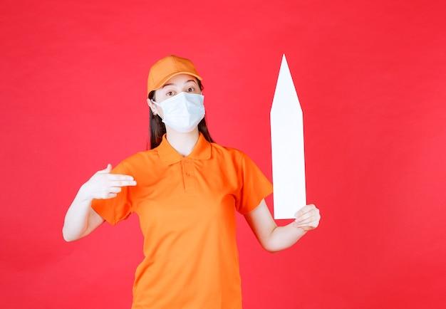 Agente di servizio femminile in codice di abbigliamento di colore arancione e maschera con una freccia rivolta verso l'alto