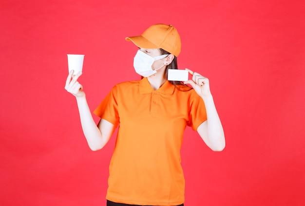 Agente di servizio femminile in codice di abbigliamento e maschera di colore arancione che tiene una tazza usa e getta e presenta il suo biglietto da visita.