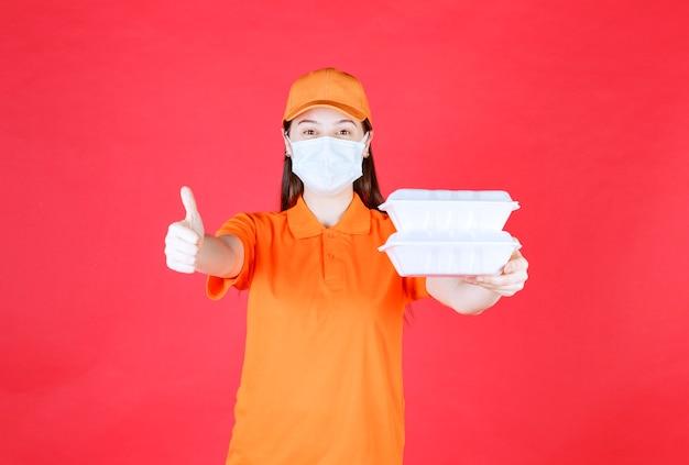 Agente di servizio femminile in codice di abbigliamento e maschera di colore arancione che tiene in mano due pacchetti di cibo da asporto e mostra un segno positivo con la mano