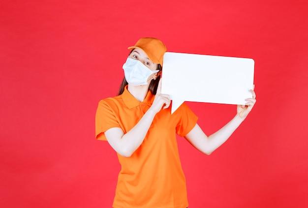 Agente di servizio femminile in codice di abbigliamento di colore arancione e maschera con una scheda informativa rettangolare bianca.