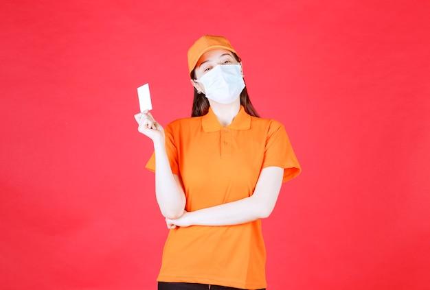 Agente di servizio femminile in codice di abbigliamento di colore arancione e maschera che presenta il suo biglietto da visita.