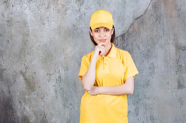 Agente di servizio femminile in uniforme gialla in piedi sullo sfondo del muro di cemento e sembra confuso e pensieroso