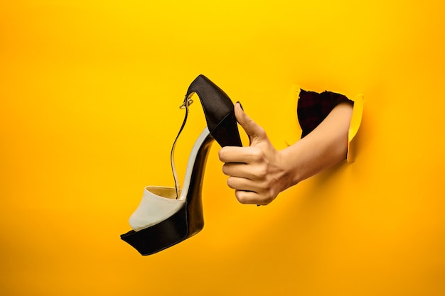 La scarpa femminile a portata di mano attraverso una carta gialla strappata