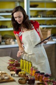 Assistente di negozio femminile che organizza la bottiglia di olio d'oliva tenendo la tavoletta digitale