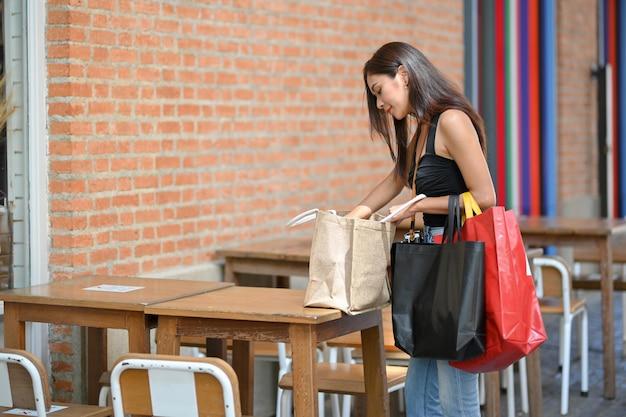 Cliente femminile che mette la borsa della spesa sul tavolo e trova qualcosa che tiene la borsa della spesa fanatica dello shopping