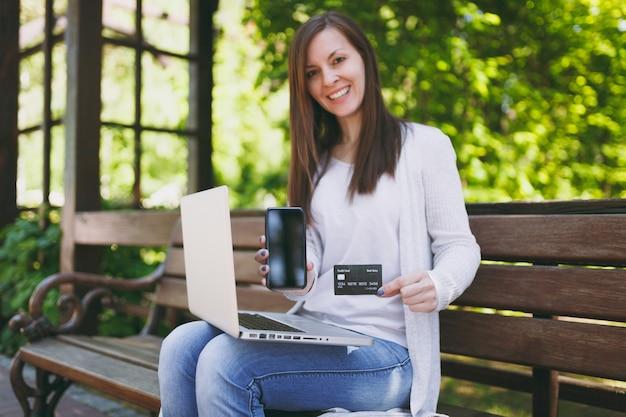 Femmina che mostra sulla carta di credito della fotocamera, telefono cellulare con schermo vuoto vuoto per copiare lo spazio. donna seduta su una panchina che lavora al computer portatile moderno in strada all'aperto. ufficio mobile. concetto di business freelance.