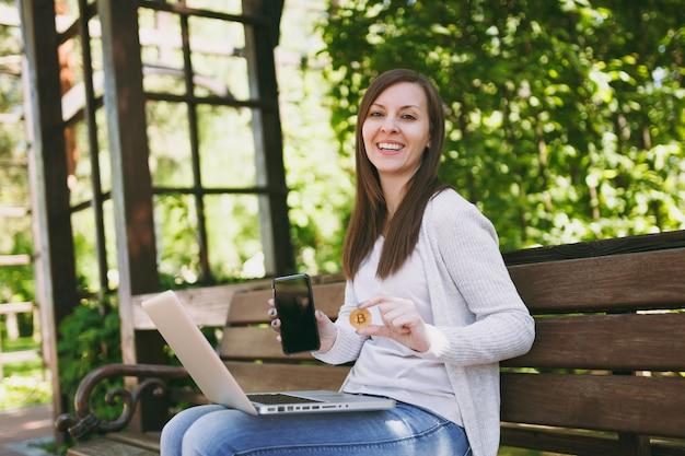 Femmina che mostra sul telefono cellulare della fotocamera con schermo vuoto vuoto per copiare lo spazio. donna seduta su una panchina che tiene bitcoin, computer portatile moderno all'aperto. ufficio mobile, concetto di valuta virtuale online.