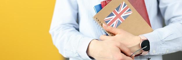 Siluetta femminile che tiene i diari con il concetto di lingue straniere di studio autonomo della bandiera britannica