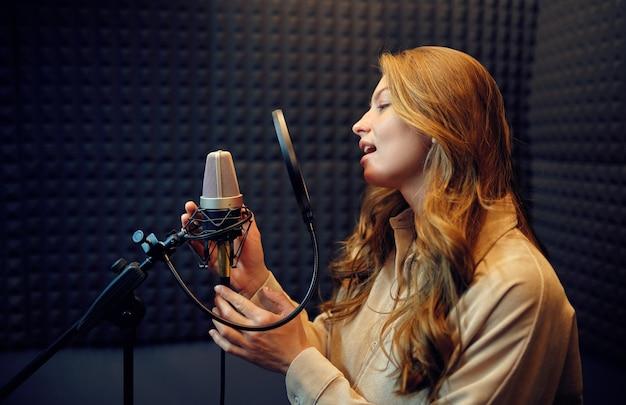 La cantante femminile in cuffia canta una canzone al microfono, all'interno dello studio di registrazione sullo sfondo. registrazione vocale professionale, posto di lavoro del musicista, processo creativo, tecnologia audio moderna