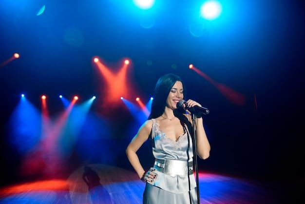 Una cantante che tiene il microfono contro le luci colorate della scena. sfondo colorato luminoso con luci al neon.