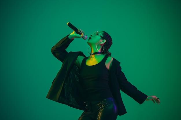Ritratto di cantante femminile isolato sulla parete verde dello studio in luce al neon