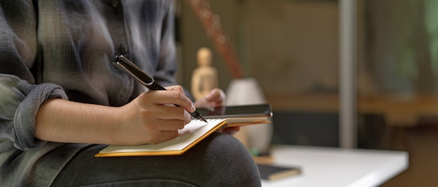 Femmina che si siede sul tavolo da lavoro e prendendo nota sul libro degli orari