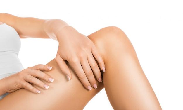 Cura della pelle femminile. donna che applica idratante sulle sue gambe perfette, isolate su fondo bianco