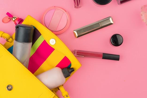 Piccola borsetta femminile piena di prodotti cosmetici su sfondo rosa brillante