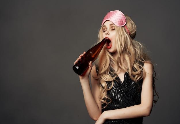 Primo piano della bottiglia dell'alcool di vita notturna del rossetto spalmato femminile