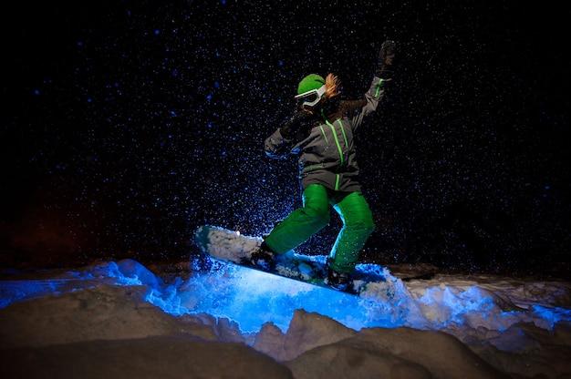 Snowboarder femminile vestito con un abbigliamento sportivo verde che salta sul pendio della montagna nella notte sotto la luce blu