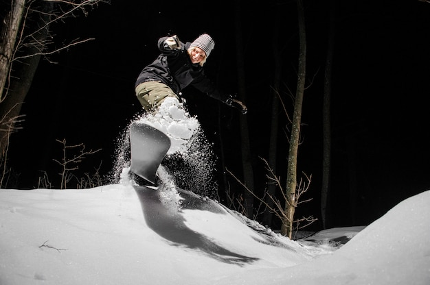 Snowboarder femminile che guida giù il pendio di montagna di notte