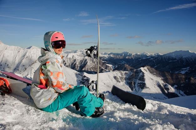 Snowboarder femminile che si siede sul pendio con gli occhiali protettivi vicino all'attrezzatura nella famosa località turistica di gudauri in georgia