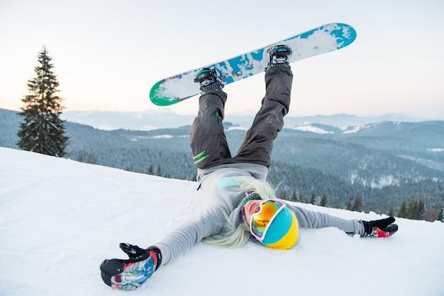 Snowboarder femminile sul pendio in montagna