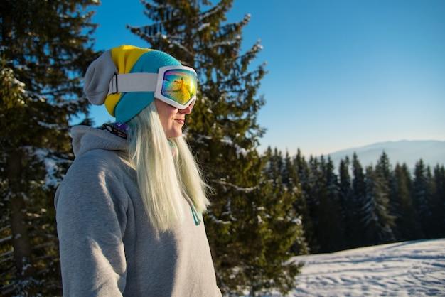 Snowboarder femminile presso la montagna innevata