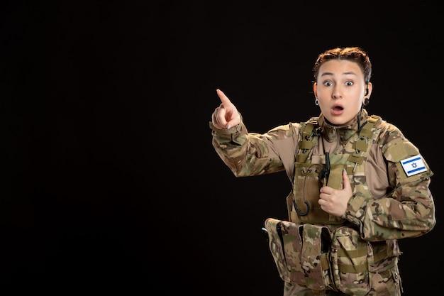 Soldato femminile in camuffamento sulla guerra israeliana del carro armato militare della parete nera