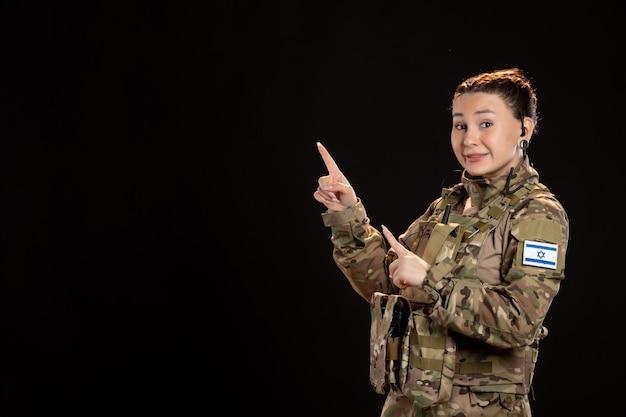 Soldato donna in mimetica sul muro nero