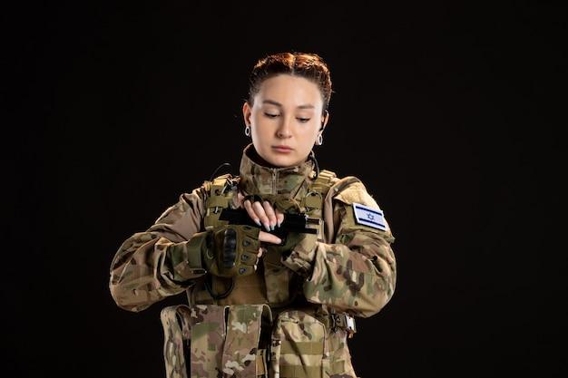 Soldato femminile in mimetica che ricarica la pistola sul muro nero