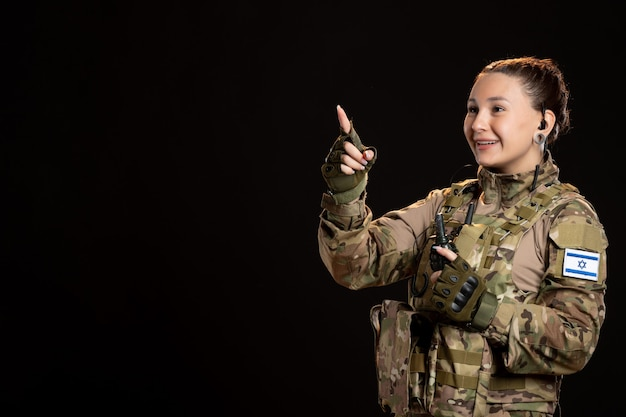 Soldato donna in mimetica con granata sul muro nero